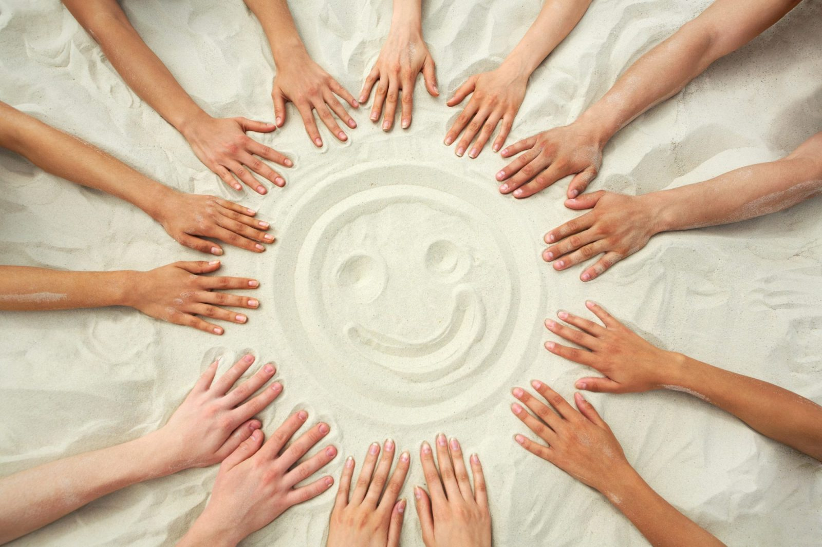 Photo Of Smiling Face Hands Painting On Sand Surrounded Human Hands