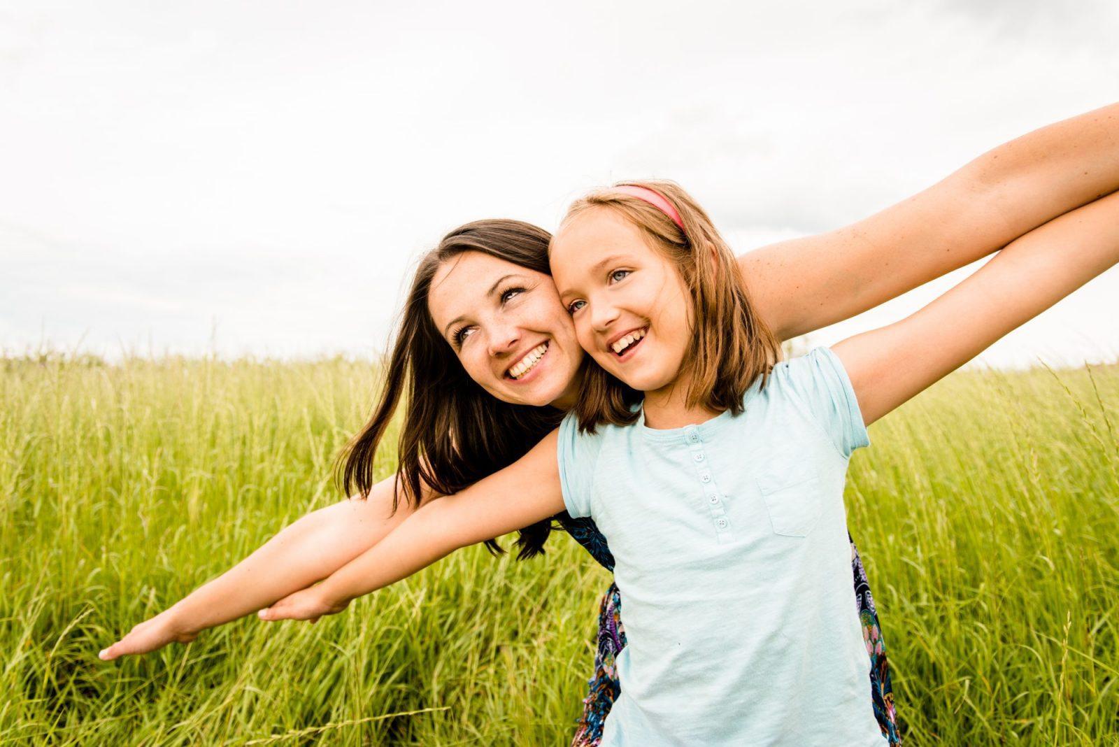 Meisje samen met moeder vrolijk in gras: Vergroot het zelfvertrouwen van je kind!