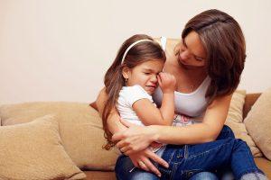 Meisje verdrietig bij moeder op schoot - omgaan met onzeker kind van 4, 5 of 6 jaar