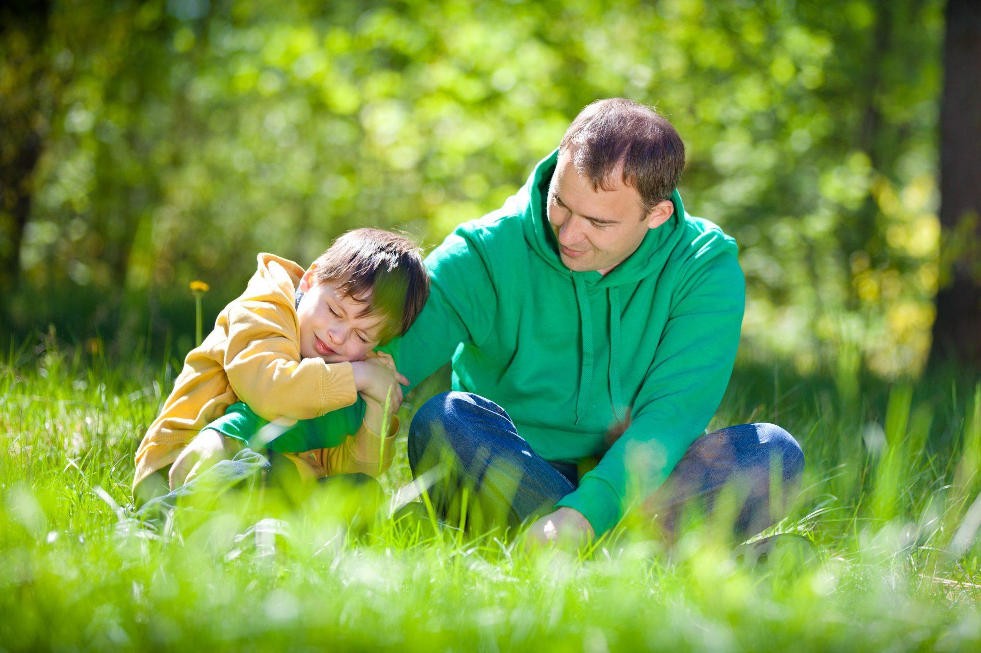 vader helpt verdrietig kind buiten